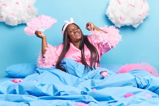 Kobieta wyciąga ręce w łóżku trzyma wentylator lubi leniwy dzień w wygodnym łóżku uśmiecha się szeroko ubrana w jedwabny różowy szlafrok opaska na głowę pozuje pod kocem białe chmury na głowie