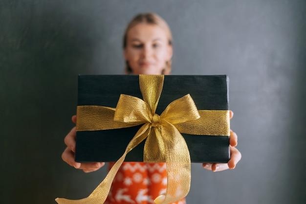 Kobieta wyciąga rękę z pudełkiem i daje prezent