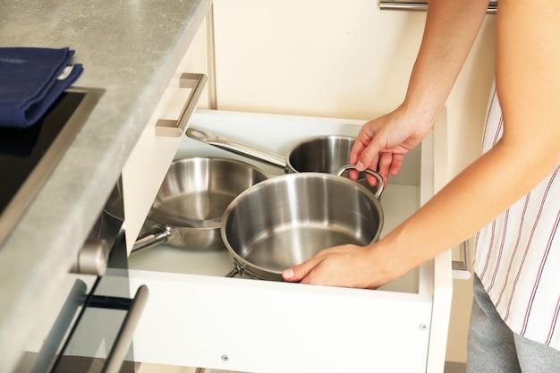 Kobieta wyciąga rondel ze stołu kuchennego.
