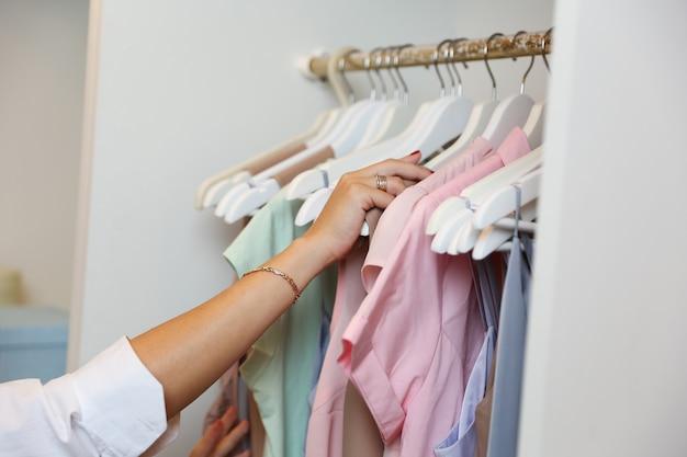 Kobieta wyciąga z szafy wieszak z ubraniami