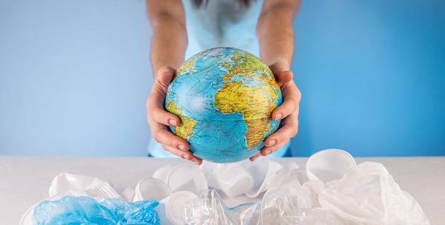 Kobieta wyciąga ziemię w formie kuli ziemskiej ze stosu plastikowych śmieci