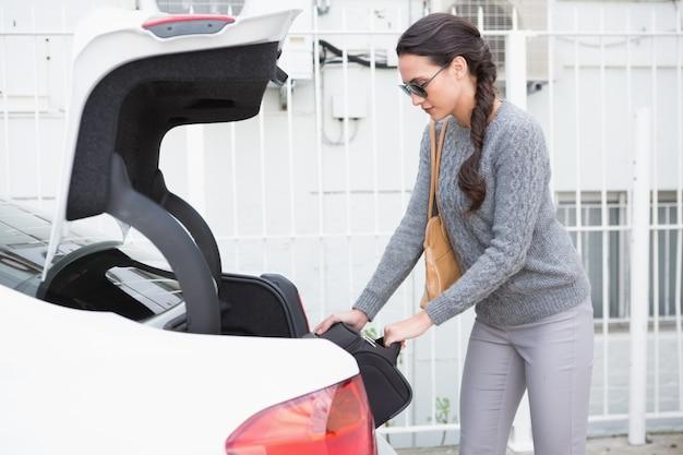 Kobieta wyciągając bagaż z bagażnika samochodu