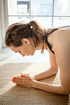 Kobieta wyciągając się do przodu, wykonując pozę jogi na macie. kobieta fitness wykonywania jogi w domu, skupić się na rękach.