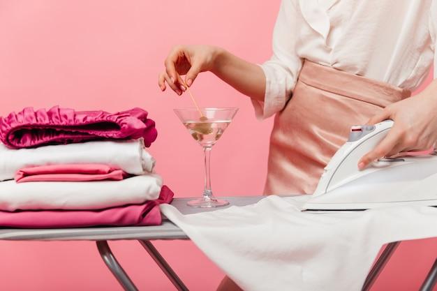 Kobieta wyciągająca oliwkę ze szkła martini i prasująca bieliznę