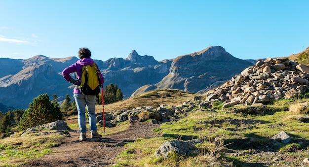 Kobieta wycieczkowicz chodzi w pyrenees górach blisko pic ossau