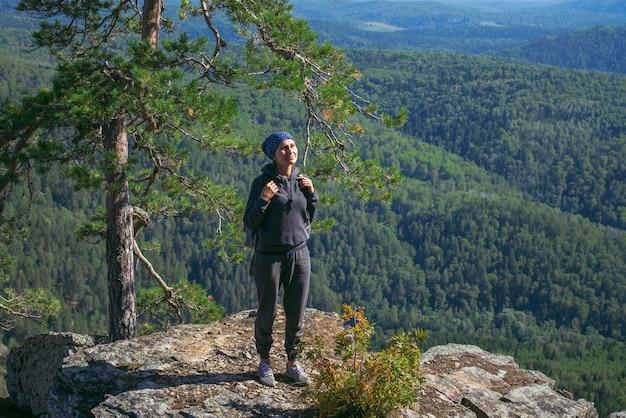 Kobieta wycieczkowicz cieszy się widok od wierzchołka góra w pogodnym letnim dniu
