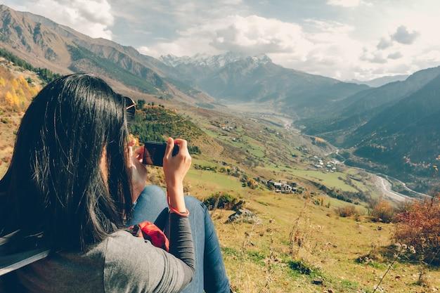 Kobieta wycieczkowicz ma piękny malowniczy widok na dolinę miasteczka.