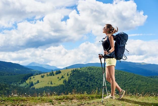 Kobieta wycieczkowicz wycieczkuje na trawiastym wzgórzu w górach
