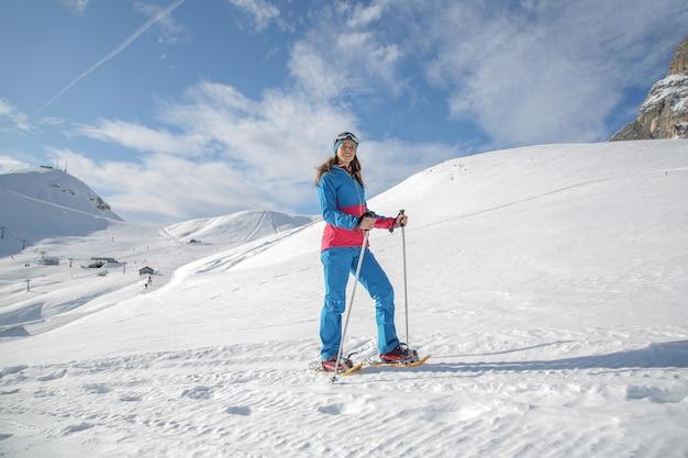 Kobieta wycieczkuje z rakietami śnieżnymi w górze