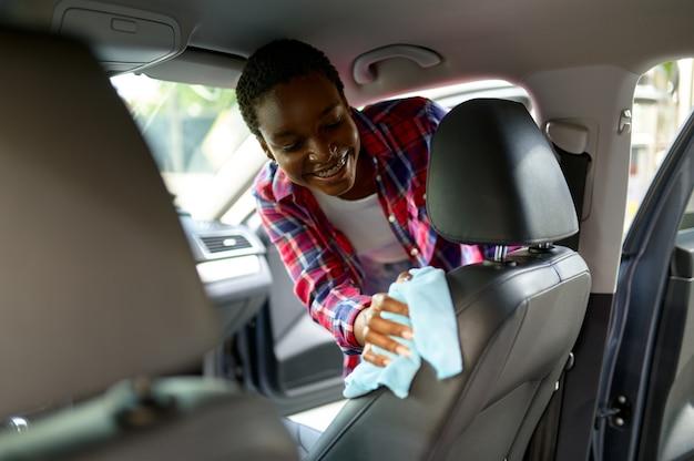 Kobieta wyciera fotelik szmatką, myjnia samochodowa