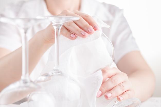 Kobieta wyciera kieliszki do wina