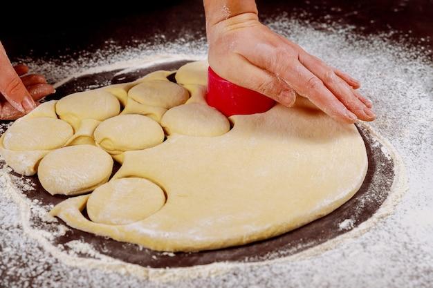 Kobieta wycina ciasto za pomocą okrągłej formy do robienia słodkich bułeczek, orzechów włoskich.