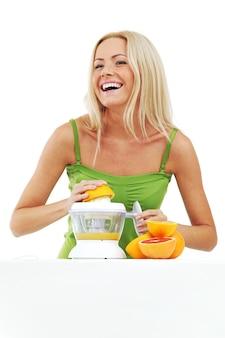 Kobieta wyciska sok sokowirówką