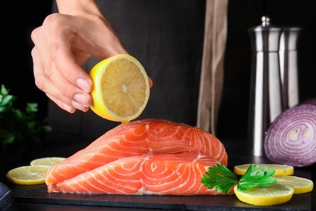 Kobieta wyciskanie cytryny na świeżego surowego łososia przy stole, zbliżenie. przysmak rybny