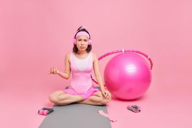 Kobieta wygląda na zaskoczoną, siedzi w pozycji lotosu, słucha muzyki przez słuchawki, ma regularne treningi fitness w domu na karemacie