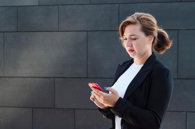 Kobieta wygląda na zdenerwowaną, niezadowoloną z telefonu. dziewczyna otrzymuje i czyta złe wieści. dama patrzy z obrzydzeniem na smartfona.