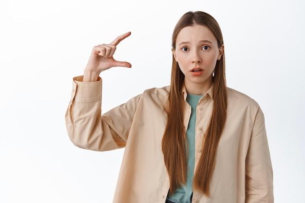 Kobieta wygląda na zdezorientowaną, pokazując drobny gest, drobiazg na copyspace, gapi się na przód zdziwiona, rozczarowana rozmiarem, stoi nad białą ścianą