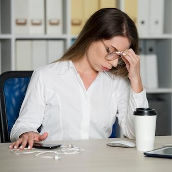Kobieta wygląda na zmęczoną w pracy z powodu czasu spędzanego przez telefon