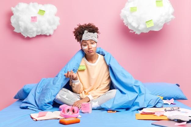 Kobieta wygląda oburzona podnosi dłoń w piżamie maska do spania siedzi w pozycji lotosu na wygodnym łóżku odrabia pracę domową w domu otoczona naklejkami z pamiętnika i kartkami