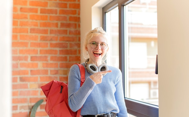 Kobieta wygląda podekscytowana i zaskoczona, wskazując na bok i do góry, aby skopiować miejsce