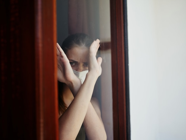 Kobieta wygląda przez okno z rękami skrzyżowanymi przed sobą