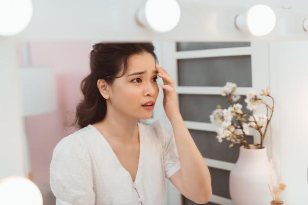 Kobieta wyglądająca jak lustro czuje się zdenerwowana i dotyka jej twarzy z problemem trądziku