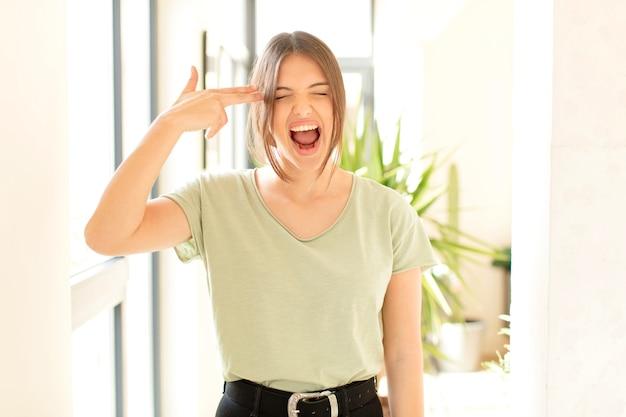 Kobieta wyglądająca na niezadowoloną i zestresowaną, samobójczy gest wykonujący znak pistoletu ręką, wskazujący na głowę