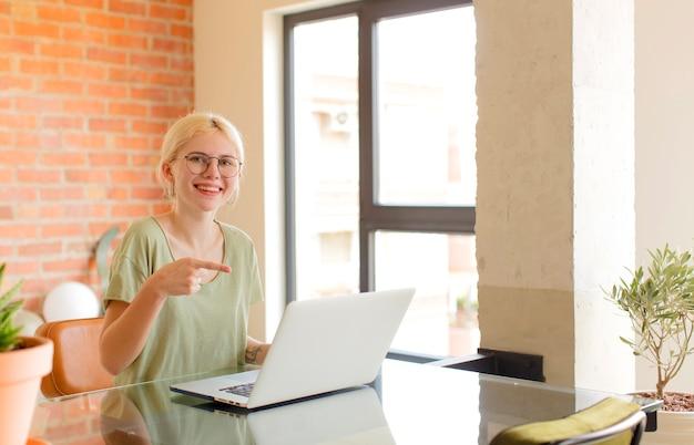 Kobieta wyglądająca na podekscytowaną i zaskoczoną, wskazując na bok i w górę, aby skopiować przestrzeń