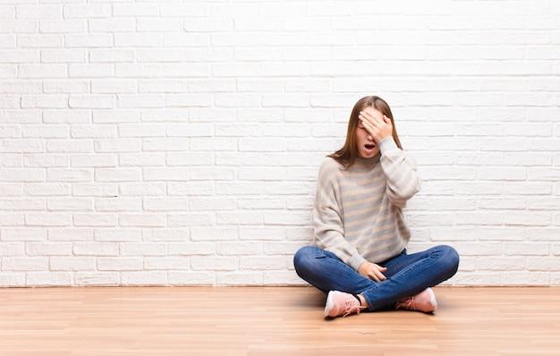 Kobieta wyglądająca na senną, znudzoną i ziewającą, z bólem głowy i jedną ręką zakrywającą połowę twarzy