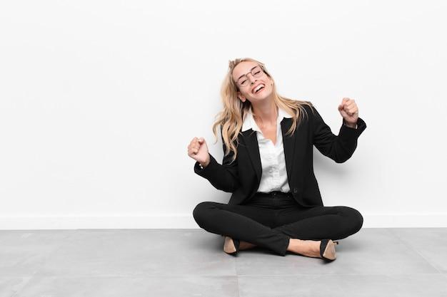 Kobieta wyglądająca na wyjątkowo szczęśliwą i zaskoczoną, świętującą sukces, krzyczącą i skaczącą