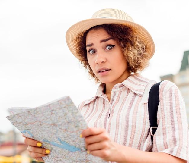Kobieta wyglądająca na zagubioną po sprawdzeniu mapy