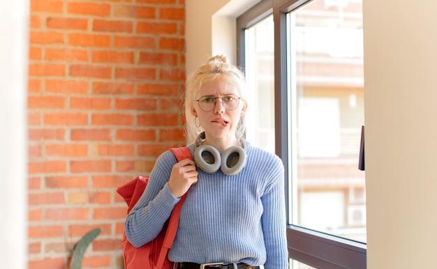 Kobieta wyglądająca na zdziwioną i zdezorientowaną, przygryzając wargę nerwowym gestem, nie znając odpowiedzi na problem