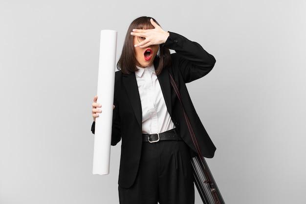 Kobieta wyglądająca na zszokowaną, przestraszoną lub przerażoną, zakrywa twarz dłonią i zerka między palcami
