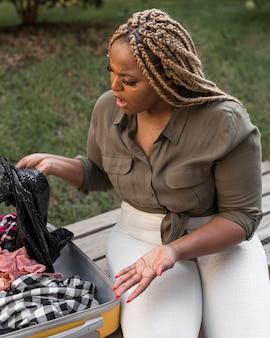 Kobieta wyglądająca na zszokowaną, widząc, jak otwiera bagaż