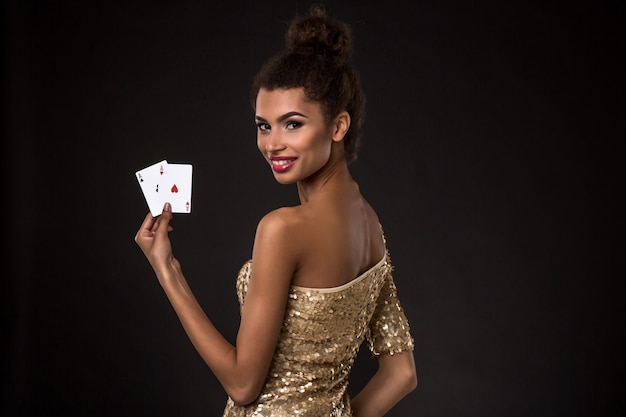 Kobieta wygrywająca - młoda kobieta w eleganckiej złotej sukience trzyma dwa asy, kombinacja kart w pokera asów.