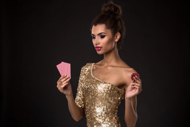 Kobieta wygrywająca - młoda kobieta w eleganckiej złotej sukience, trzymająca dwie karty i dwa czerwone żetony, kombinacja kart w pokera asów.