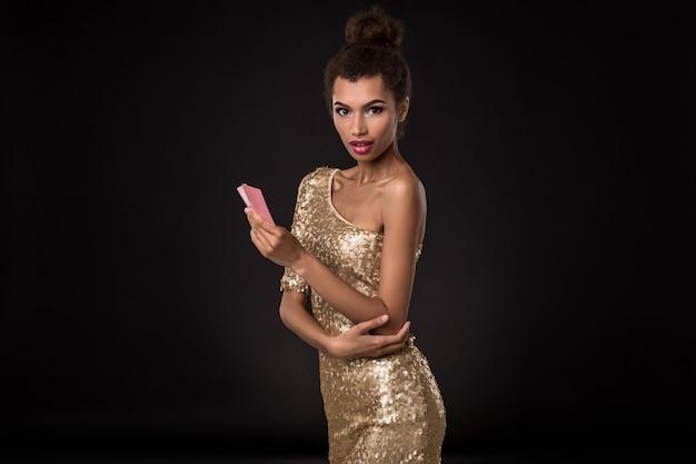 Kobieta wygrywająca - młoda kobieta w eleganckiej złotej sukience trzymająca dwie karty, kombinacja kart w pokera asów. emocje