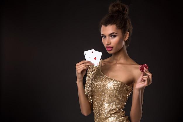 Kobieta wygrywająca - młoda kobieta w eleganckiej złotej sukience z dwoma asami i dwoma czerwonymi żetonami, kombinacja kart w pokera asów.