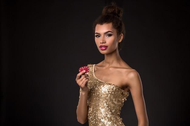 Kobieta wygrywająca - młoda kobieta w eleganckiej złotej sukience z dwoma czerwonymi żetonami, kombinacja kart w pokera asów.