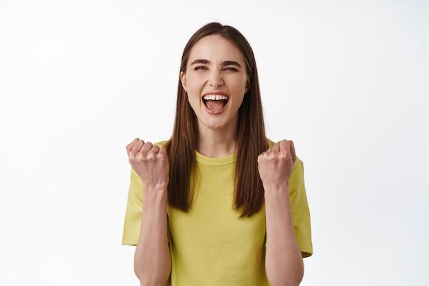 Kobieta wygrywająca, triumfująca, krzycząca z radości z wygranej, świętująca zwycięstwo, stojąca radośnie na białym tle