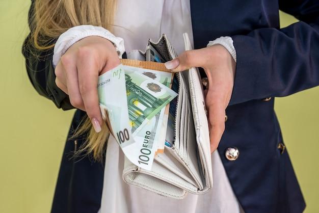 Kobieta wyjmuje banknoty euro z portfela na zielono