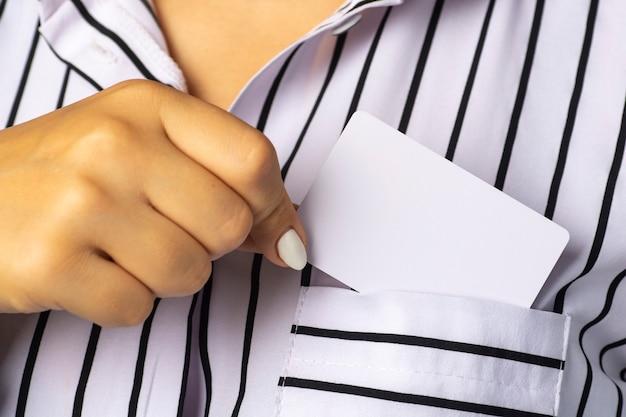 Kobieta wyjmuje białą wizytówkę z kieszeni bluzki.