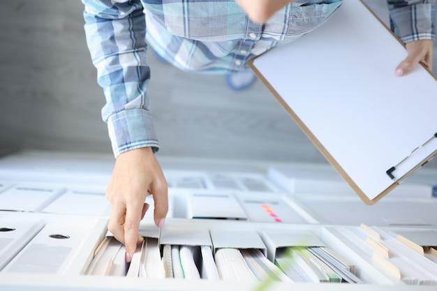 Kobieta wyjmuje dokumenty biznesowe z gabinetu z bliska