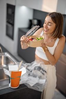 Kobieta wyjmuje jedzenie z opakowania w kuchni