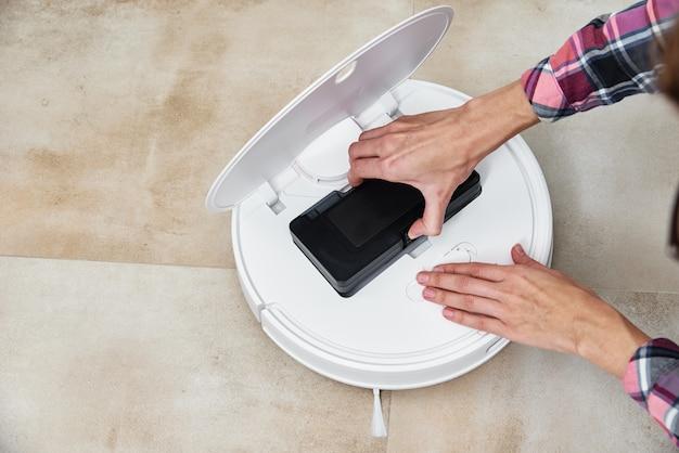 Kobieta wyjmuje pojemnik na kurz w odkurzaczu automatycznym. serwis sprzętu agd