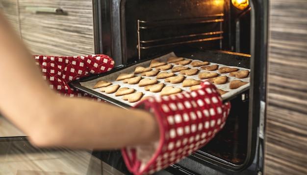 Kobieta wyjmuje z piekarnika blachę z pysznymi ciasteczkami w kształcie serca