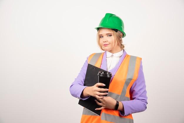 Kobieta wykonawca w kask ze schowka i kubek czarny na białym.