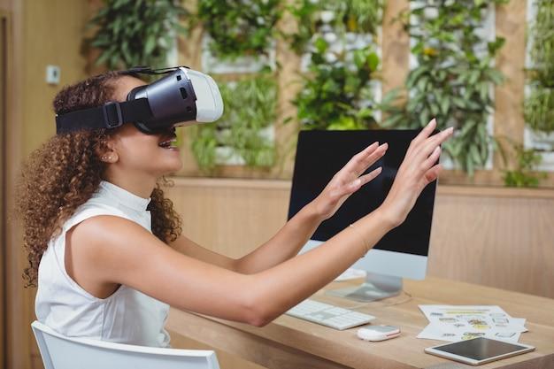 Kobieta wykonawczy za pomocą zestawu słuchawkowego wirtualnej rzeczywistości