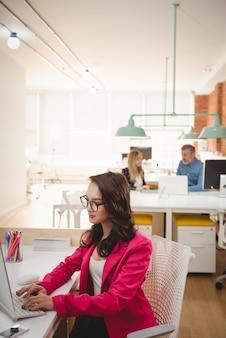 Kobieta wykonawczych za pomocą laptopa przy biurku