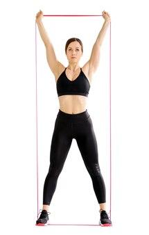 Kobieta wykonująca ćwiczenia na siłowni z opaską wzmacniającą i ujędrniającą jej mięśnie